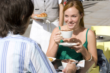 Young couple at cafe, outdoors, woman smiling at man