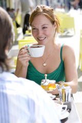 Young couple with coffee in cafe, woman smiling at man