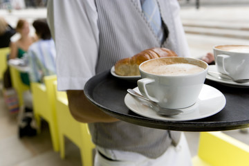 Waiter with coffee and croissant on tray, mid section