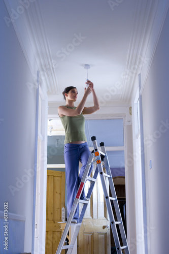Woman on ladder changing light bulb, low angle view
