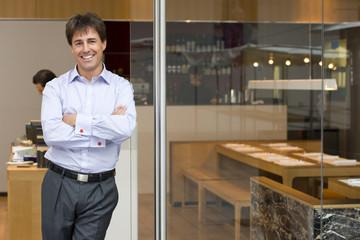 Businessman in doorway of restaurant, smiling, portrait