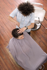 Man having haircut by barber, elevated view
