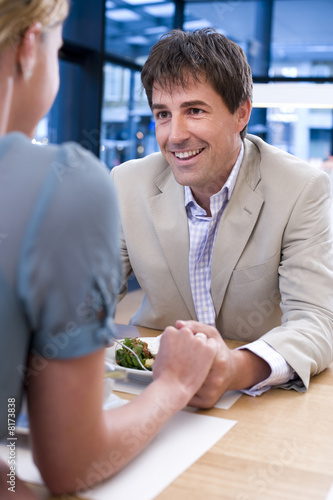 Couple holding hands at table in restaurant