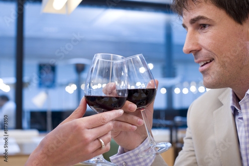 Couple proposing toast with wine glasses in restaurant, close-up
