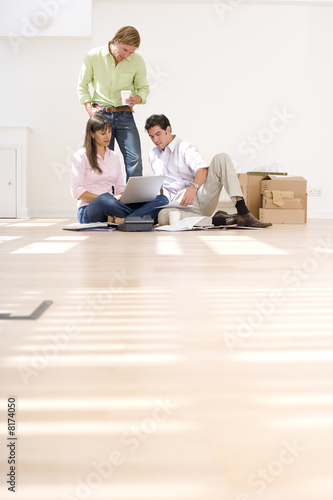 Man and colleague looking at woman's laptop computer by boxes