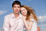 Portrait of a young happy couple against a backdrop of blue sky poster