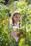 Girl (8-10) in vegetable garden, portrait