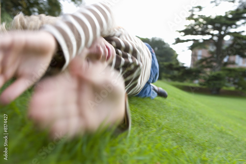 Boy (10-12) rolling down hill
