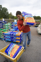 Man in garden shop with bag of soil