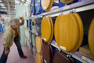 Senior man looking at toilet seats in shop