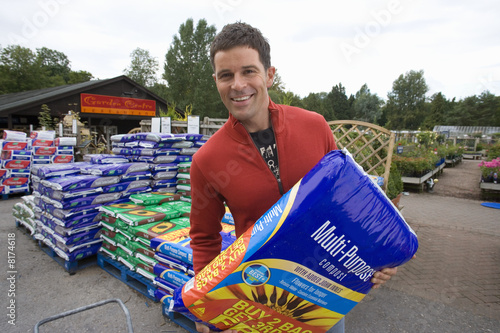 Man with bag of compost, smiling, portrait