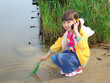 Little girl on the riverside. Game and mobile communication.