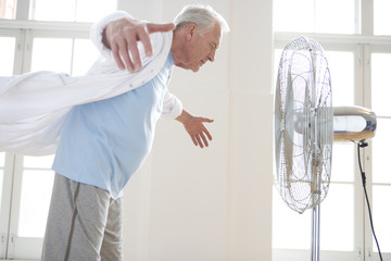 Senior man with arms outstretched by fan, side view