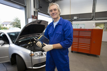 Mechanic with electronic diagnostics device by car, smiling, portrait