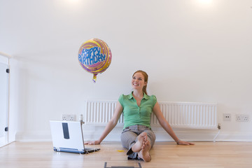 Woman with laptop computer and 'Happy Birthday' balloon, smiling