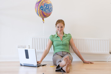 Woman with laptop computer and 'Happy Birthday' balloon, smiling, portrait