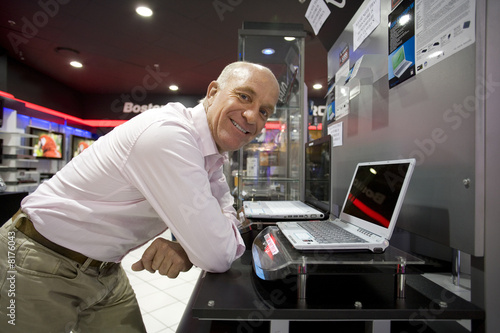Man by laptop computer in electronics shop, smiling, portrait
