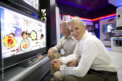 Senior couple by flat screen in electronics shop, portrait of woman