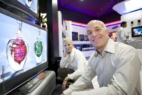 Senior couple by flat screen in electronics shop, portrait