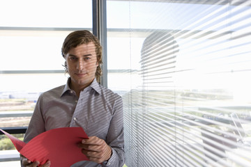 Businessman with file by window, portrait