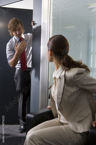 Businesswoman in chair looking at businessman at door