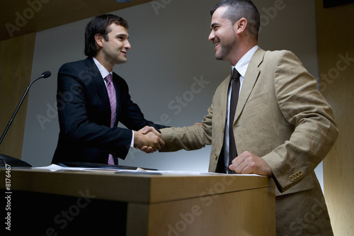 Businessman shaking hands with colleague by lectern, low angle view