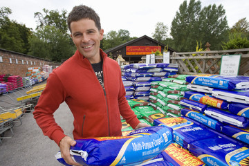 Man with bag of soil in garden center, smiling, portrait