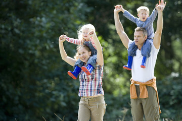 Couple with son and daughter (2-4) on shoulders outdoors