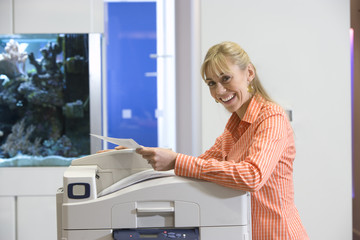 Woman at photocopier by fish tank, smiling, portrait