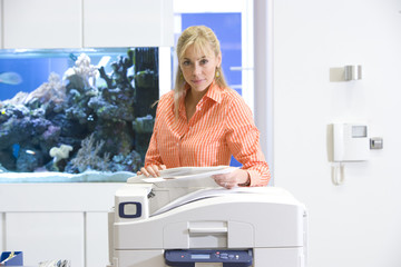 Woman at photocopier by fish tank, portrait
