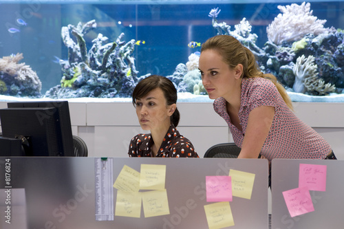 Woman and colleague at workstation, fish tank in background