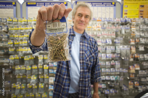 Man with bag of screws in hardware store, portrait