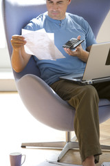 Man with paperwork and laptop computer in armchair