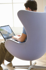 Man with laptop computer in armchair, rear view
