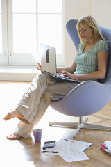 Woman with laptop computer in armchair