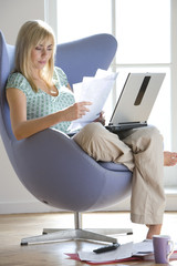 Woman with laptop computer and paperwork in armchair, low angle view