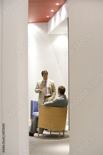 Businessman in conversation with colleague in chair