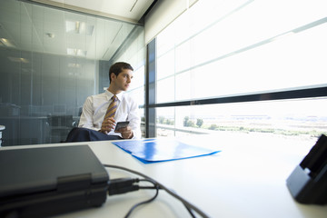 Businessman using electronic organizer in office