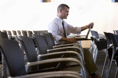 Businessman with laptop in empty lecture hall