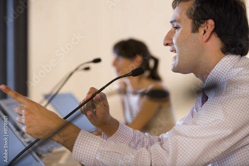 Businessman speaking into microphone at conference