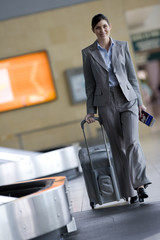 Businesswoman pulling luggage in airport baggage claim