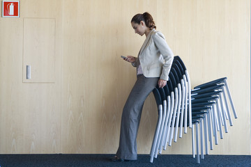 Woman checking text messages while leaning on stack of chairs