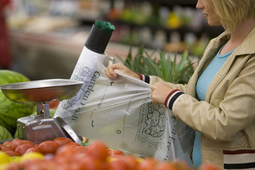 Woman tearing off plastic bag in grocery store