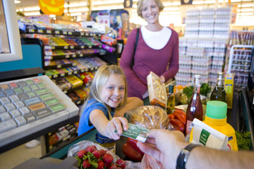 Girl handing credit card to cashier in grocery store