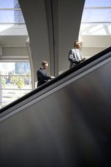 Businessmen using escalators in airport