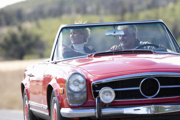 Senior couple on road trip driving red convertible