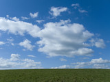 Blue sky, clouds and green field