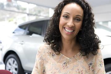 woman smiling in car showroom
