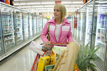 Woman grocery shopping in frozen foods section