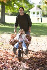 Father wheeling daughter in wheelbarrow in autumn